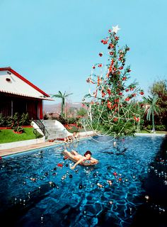 by Slim Aarons. Rita Aarons, wife of photographer Slim Aarons, on a lilo in a swimming pool decorated for Christmas, Hollywood, 1954 Christmas In La, Christmas Style, Retro Christmas, Family Christmas, Christmas Photos, Summer Christmas, Tropical Christmas, Aussie Christmas, Celebrating Christmas