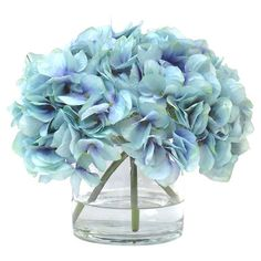 Add a touch of floral romance to your dining table or mantel with this elegant arrangement, showcasing faux hydrangea nestled in a glass vase.