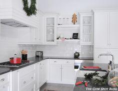 Custom White Cabinetry decorated for Christmas! Subway Tile Backsplash, Black Leathered granite, Farm Sink & Open shelving.