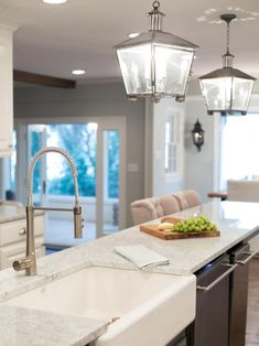 While the lantern pendants stay true to the Sanders' French country aesthetic, the kitchen has been updated with sleek white marble countertops, a brand new apron sink and modern fixtures. The island also provides a spacious serving surface for parties.