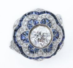 A fine Art Deco style diamond and sapphire cluster ring mounted in platinum, the centre set with an old brilliant cut diamond single stone weighing approximately 1:10 carats within a scalloped calibre cut cabochon sapphire and diamond surround with an outer border of calibre cut sapphires
