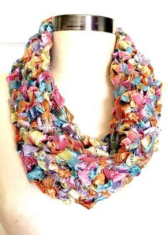 """Pastel Rainbow Infinity Scarf Handmade Single Loop Scarf. Crocheted Knitted Ribbon. Pastel Rainbow colored, ribbon infinity scarf. These lightweight infinity scarves are great accessories that can be used as a statement piece to help enhance or change your outfit up completely. It is fiber jewelry and a scarf all in one that also looks like a necklace. These """"put over your head and go"""" scarves are extremely comfortable and versatile. They can be worn casually with a tee shirt and jeans or..."""