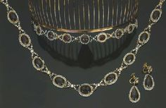 """Garnet and cultured pearls parure of a necklace with graduated oval garnets surrounded by small pearls, beads, a pair of earrings and a tiara """"en suite"""", gold mount and silver gilt, stamp Rome 1811 -1814 (Christies)"""