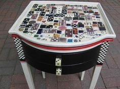 """Etsy Art Play, upcycled vintage painted mosaic table: """"The top contains game pieces, resin coated """"art"""" images of Frida Kahlo and others, china shards, bits of vintage jewelry and other tiny treasures."""""""