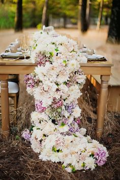 Centre de table avec décoration florale composée d'une cascade de fleurs pour un beau mariage estival et champêtre.