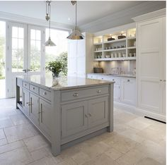 This bright and light shaker style kitchen is painted in bespoke Tom Howley paint colour; Chicory, the light Ivory Spice granite worktops and Mazzano Tumbled marble flooring create a heightened sense of space.