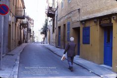 PATIENCE IN PHOTOGRAPHY... I waited for this shot.... A man on a street near the base of the Acropolis in Athens... passing by a place called Zorba's - which put me in mind of the late great actor Anthony Quinn - who starred in Zorba the Greek.  -- www.melawend.com