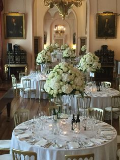 White and green table centres in the Long Gallery at Castle Howard created by Queens Flowers