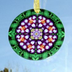Iris sacred geometry mandala kaleidoscope glass suncatcher titled Faithfully Yours. <br /> <br />This stunning iris beveled glass sun catcher illuminates my geometric mandala kaleidoscope design when light shines through it! It is 3 - ½ inches in diameter and has a beveled edge. The Suncatcher comes with a ribbon and suction cup for hanging. <br /> <br%2...