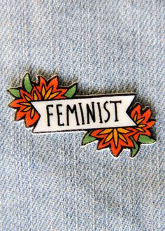 "This bold and beautiful lapel pin features the quote, ""feminist"" on a black and white banner surrounded by red flowers. Each pin is printed from my original art design on durable plastic. It has a shi"
