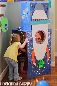 DIY Rocket ship photo booth at a space themed birthday blast off party. Use a few cardboard boxes covered in blue plastic tableclothes and spraymount a foamcore rocket ship on front. Cut a porthole in front and decorate with paper, stickers and a strand of Christmas lights.