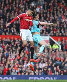 Chris Smalling of Manchester United in action with Andy Carroll of West Ham United during the Emirates FA Cup Sixth Round match between Manchester United and West Ham United at Old Trafford on March 13, 2016 in Manchester, England.