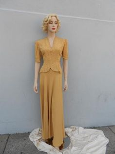 This rhinestone gown is made out of a crepe material. It has a 'V' neckline, big shoulder pads and ¾ sleeves. The dress has a very fitted bodice with a short peplum. The skirt of the dress is very full. The bodice is covered in small rhinestones. The dress zips up the side and is a size 4. This dress contains zero damages.  Price: $75