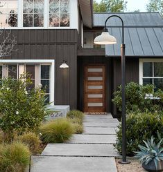 Exterior color Scheme: Dark gray paint on walls and facia and door frames, with white on windows and under eaves, warm wood front door. Dark Grey Houses, Dark House, Brown House, Ranch Exterior, Grey Exterior, Exterior Remodel, Modern Exterior Doors, Exterior Siding, House Siding