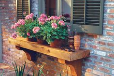 As alternatives to window boxes, the landscape architects designed wooden plant shelves. The bracketed supports attach to the house at the base of the windowsills. To anchor the terra-cotta pots and allow for drainage, pieces of 1-inch-diameter pipe are attached with epoxy into holes cut in the wood. Then the drainage holes in the bottom of the pots are set onto the pipes.