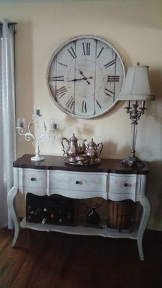 love,my new metal amd,wood rustic oversized clock from hobby lobby and my new provincial console table for buffet. displaying antique tea set, candelabra and french lamp with wine and antique grape press below. French country rustic farmhouse.