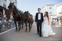 horse carriage downtown mackinac island wedding photo by Paul Retherford Photography #mackinacisland #wedding #nomiweddings #destinationwedding #islandwedding #northernmichigan #mackinaw #mackinac #horse #carriage #maggiesottero #dress #tuxedo