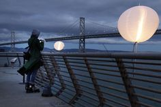 "Stefunny Pettee of San Francisco snaps a photo of the Bay Bridge from Pier 14 as she awaits the launch of ""Bay Lights."" Photo: Carlos Avila Gonzalez, The Chronicle"