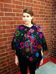 This gorgeous peacock and floral poncho is a sure show stopper and will keep you both warm and cheery on even the gloomiest of winter days. The base fabric is hand loomed and heavy yet soft. The floral and bird motifs have been cross stitched by hand into the poncho for the perfect bohemian addition to your fall or winter wardrobe. It's perfect with a pair of skinny jeans + combat boots and a big felt hat, and can also be dressed up with your favorite dress and heels for an evening out.