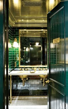 In the bathroom of Ralph Lauren's Manhattan Polo Bar, emerald-green tile and brass details lend retro glamour to a washroom