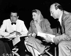Medium BTS shot of seated Humphrey Bogart as Rick Blaine, Ingrid Bergman as Ilsa Lund, and director Michael Curtiz.