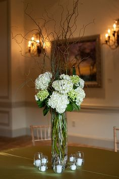 Hydrangeas and twisted stems with candles around the base. Looks lovely as you go into the evening and the design is softly uplit.