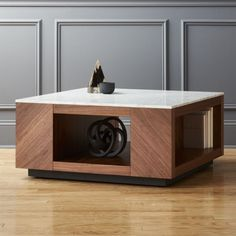 Shop Suspend II Marble and Wood Coffee Table. Designed by Ceci Thompson, this architectural form spotlights the richness of natural materials. A cool slab of white Carrara-style marble with grey veining tops the contrasting warmth of a large, square walnut veneer base.