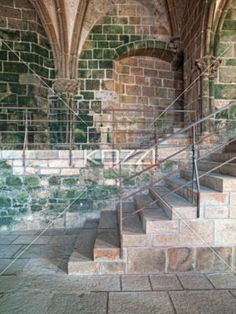 Clean Cut Staircase - Sharp stairs with older stone walls green with age leading to a platform that has a bricked up doorway and stretching ceiling supports.