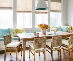 Coastal-inspired dining space with colorful bouquet as centerpiece and wicker-back chairs
