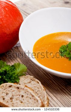 fresh tasty homemade pumpkin soup on wooden table with parsley and bread - stock photo