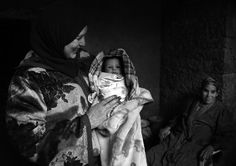 Fatima holds her very young nephew in her family's home in Tamda, Morocco.