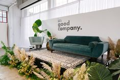 The main stage inside Gallery 308 at Fort Mason—a large cultural center overlooking the San Francisco Bay—featured a plush green sofa, a patterned rug, and greenery by Natalie Bowen Designs. Bright Event Rentals provided furniture.