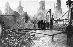 PEOPLE WALKING ALONG LITTLE PARK STREET, COVENTRY ON THE MORNING OF 15 NOVEMBER 1940. THE STREET IS BLOCKED AT THIS POINT BECAUSE OF AN UN-EXPLODED BOMB]