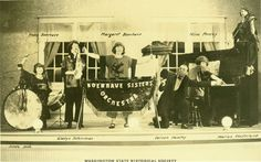 Photo of the Boerhave Sisters Orchestra from Lynden, WA, posed on stage, holding their instruments as if for a performance. Five members of the group are women, and all their names are printed beside them on the photo. The sole male, also named, holds a megaphone in his hand. Musical instruments played by the women include: piano; violin; saxophone; bass drum; snare drum; and a percussion instrument, either a marimba or xylophone. The violinist sits on top of the upright piano.
