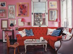 """An image of Miles Redd's famous """"red and pink"""" room — from the designer's own New York City townhouse — shows how the designer deftly paired a tufted red sofa with lipstick-pink walls."""