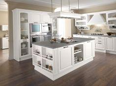 Cucina composta con isola centrale in rovere bianco con mensole vasistas.