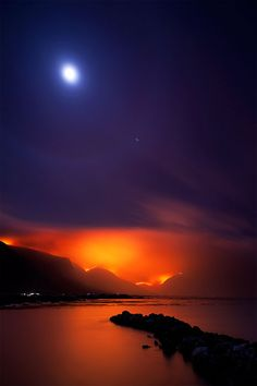 The moon and a wildfire on the mountains of Bettys Bay,Western Cape South Africa