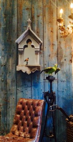 "Antique blue ""Nail-door"" with old zinc French Oeil de boeuf mirror.  Two taxidermy colourfull birds. A brown vintage leather tufted chair and a cast iron black  pedestal.  In the Showroom of Piet Jonker"