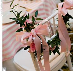 The round reception tables were topped with pink-and-white-striped tablecloths and surrounded by white chiavari chairs. To differentiate the bride and groom's chairs, the seat backs were wrapped with vines, pink ribbon, and pink spray roses. Green-an...