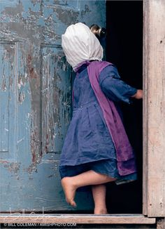 Little amish girl looks like she's skipping in the house. Cute!
