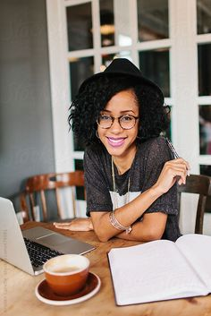 Businesswoman using her laptop at a coffee shop and taking notes by Kristen Curette Hines for Stocksy United