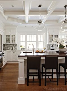 New England Home - hardwood floors, white cabinetry, millwork, coffered ceiling, coffered ceiling in kitchen, recessed lighting, pot lights, stained wood countertop, stained butcher block, stained butcher block countertop, kitchen island, prep sink, gooseneck faucet, glass fronted cabinetry, ceiling height cabinetry, marble countertops, mosaic glass backsplash, glass pendants