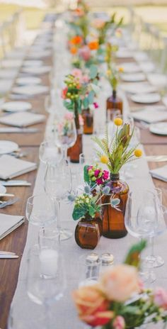Wildflowers in upcycled vessels set on textured neutral linens. Get more spring table decor ideas from @dominomag