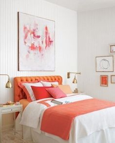 big art above bed, gallery on side wall.  unity of tangerine and white with gold frames/lights