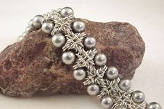 This is a beautiful chain maille bracelet that incorporates pearls or crystals along both edges -- a stunning and substantial addition to your jewelry wardrobe. Taught by Sue Ripsch. #chainmaille #beadstringing