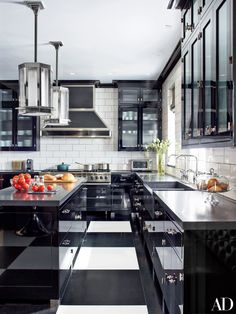 """""""I think of black, white, and red as high style,"""" says Gambrel. Thick stone countertops and simple metal hardware feel glamorous against the black lacquer cabinets, while oversize checkered floors are a play on old-time kitchens. A nearby red upholstered banquette is Gambrel's ode to a vintage steakhouse.  RELATED: Get more kitchen renovations tips and ideas from AD."""
