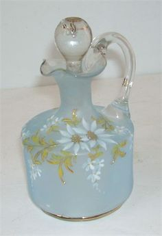 Pale Blue satin glass vinegar cruet with applied handle   White painted on daisies with gold trim,    Makers flaw- Cut off process on the stopper is very choppy at the end  On the round top of the stopper the glass did not flow into the mold and  left a u shaped dent in the glass at the very top.  Also on the handle the glass did not flow in the mold  and left a small vertical line.   The bottom part of the cruet in good condition with no chips, cracks or  others issues.   A pretty hand…