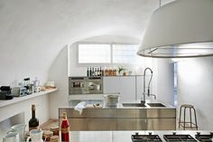 The minimalist bright white modern kitchen of this Italian vacation home in Salento showcases a sleek steel cabinet system and a Kono hood from Elmar.