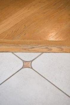 Hardwood and tile often lay at the same height, making transitions simple. How to lay hardwood next to tile flooring. .Might do this for the entrance and the area between the island and main kitchen counter/sink area
