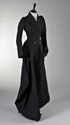 A lady's riding habit, English, circa 1890, comprising heavily boned navy wool double breasted jacket, label removed but the skirt with 'William Scott, 2 Lower Sackville St, Dublin', Miss Dundas, with tiny waist and full skirts; with faux waistcoat chemisette in checked wool, and shaped matching skirt, bust 81cm, 32in, waist 46cm, 18in, (3)